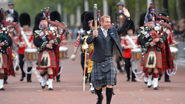 Sir Chris Hoy carries the Commonwealth Games Baton